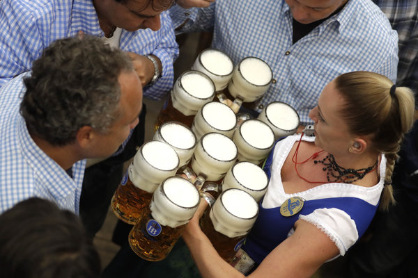 Čašníčka nesie poháre piva.