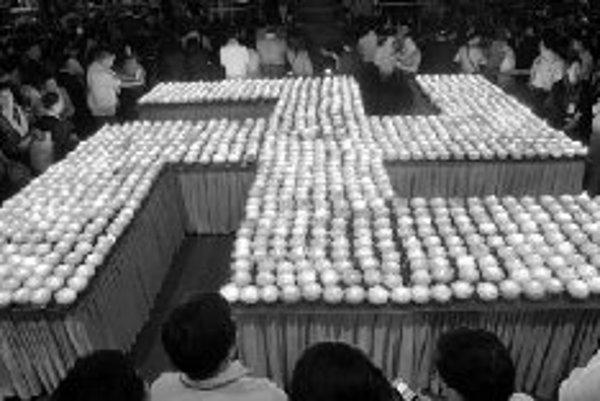 Budhistickí veriaci na ceremónii na počesť Budhových narodenín pred svastikou, niekoľkotisícročným symbolom šťastia a znovuzrodenia, ktorého sa v 20. storočí zmocnili nacisti.