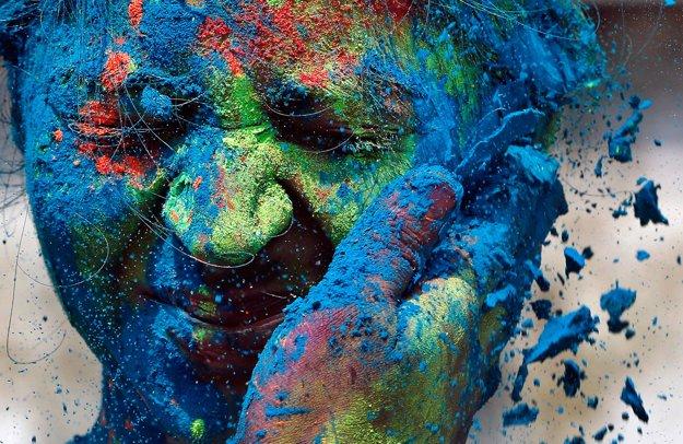 Muž hádže farbu na tváre ženy počas osláv indického sviatku Hólí.