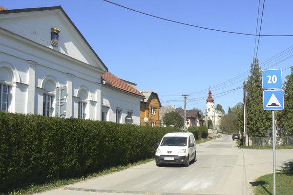 Na snímke na ľavej strane klasicistická kúria, v pozadí rímskokatolícky kostol ku cti Povýšenia sv. Kríža.