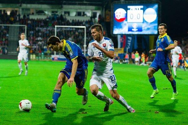 Michal Ďuriš sa snaží získať loptu od jedného z ukrajinských hráčov.