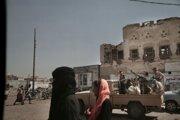 Obyvateľky prístavného mesta Hudajdá kráčajú popri hliadke koalície bojujúcej proti povstalcom.