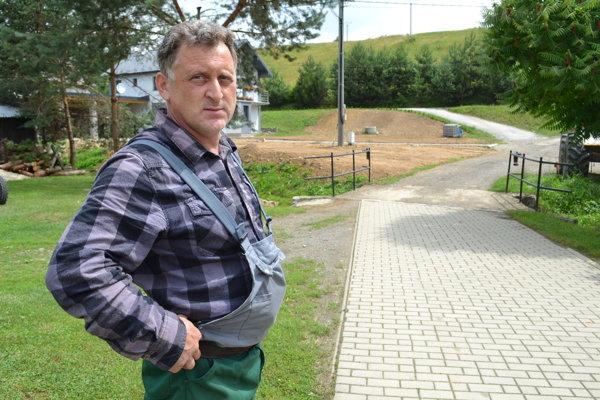 Jozef Bučko ukazuje na úsek cesty, ktorý ostal bez asfaltu.