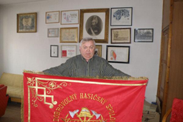 Dnešný šéf miestnych dobrovoľných hasičov Ján Gärtner a nad ním v ráme portrét Ladislava Tombora.