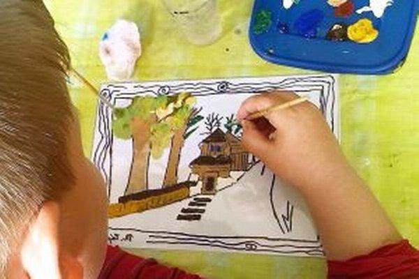 Pod rukami žiaka vyrastá drevený evanjelický kostol v Leštinách.