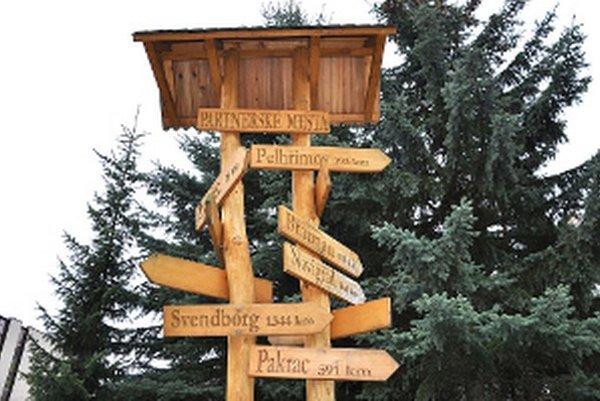 Smerovníky na stĺpe označujú vzdialenosti a smer partnerských miest.