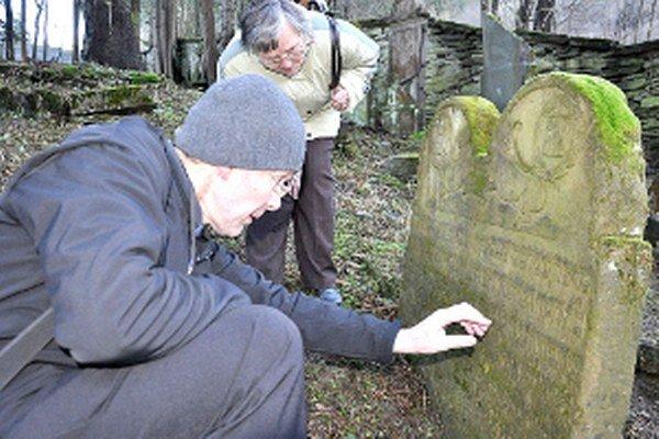 Mikuláš Lipták pozorne študuje nápis na jednom zo starých pomníkov.