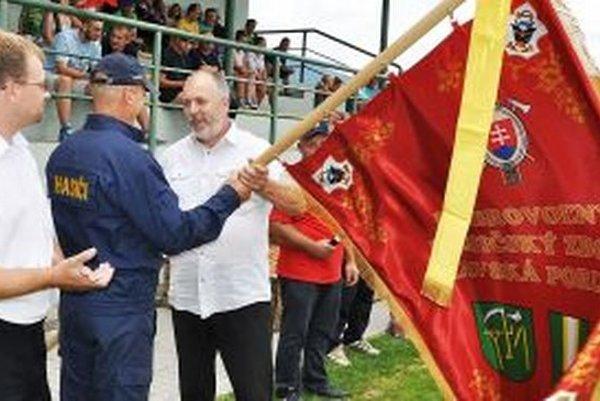 Zástavu prebrerá z rúk starostu Petra Hrivnáka predseda DHZ Albín Michalica.