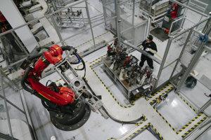 Zamestnanec Tesly pripravuje komponenty, ktoré sa stanú súčasťou palubnej dosky Modelu X.