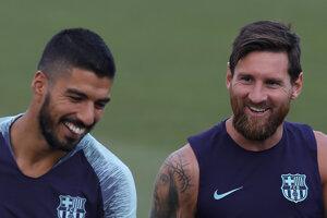 Lionel Messi (vpravo) počas tréningu žartuje so spoluhráčom Luisom Suárezom.