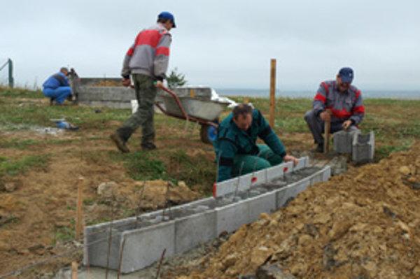 Zamestnanci obce začali murovať plot okolo budúceho cintorína.