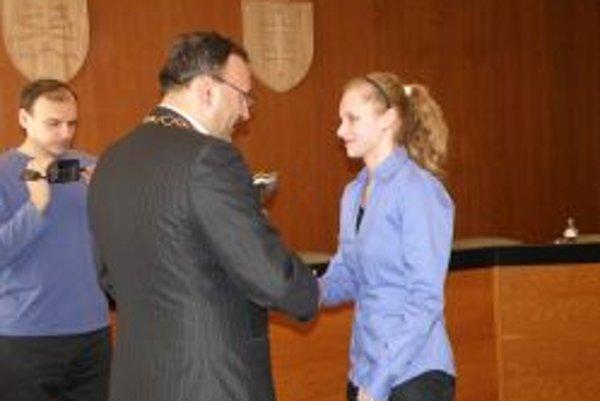 Lenka Kmotorková preberá ocenenie z rúk primátora Topoľčian Petra Baláža.