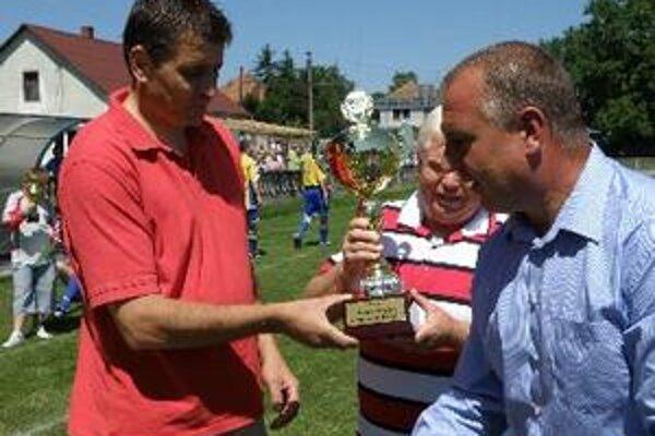 Tréner Roman Patrovič a starosta Krušoviec Ivan Hubinský preberajú pohár za prvé miesto z rúk predsedu ObFZ Topoľčany Pavla Šípoša.