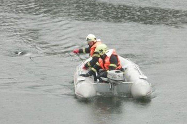Hasiči vyťahujú utopeného muža na breh.