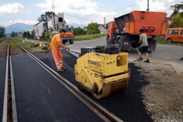 V okolí koľají natiahli chlapi nový asfalt.
