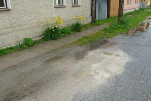 V pieskom zasypaných jamách sa drží dažďová voda, ktorú autá vyšplechujú na domy.