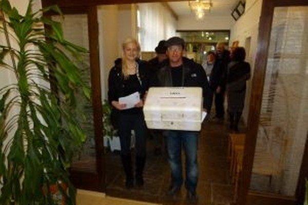 Členovia okrskovej komisie č. 2 v Turanoch sa vracajú s prenosnou urnou do volebnej miestnosti.