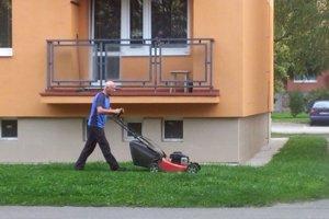 Dôchodca kosí okolo bytovky na Kubínskej ulici na sídlisku Vlčince.