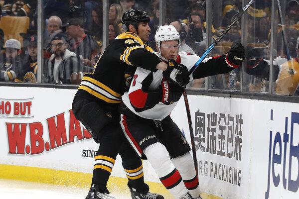 Kapitán Bostonu Bruins Zdeno Chára (vľavo) v súboji s Bradym Tkachukom z Ottawy.