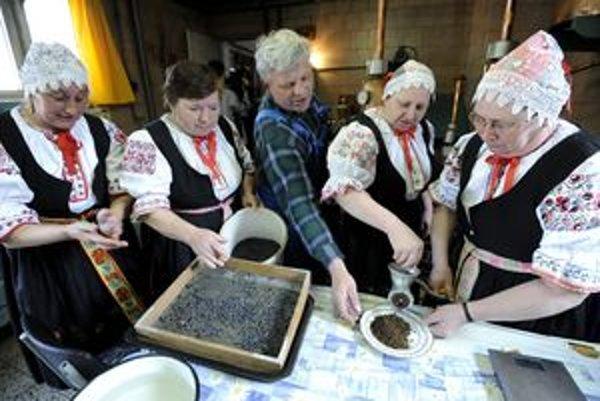 Záver sezónyŽeny z miestnej folklórnej skupiny Ledničanka spievajú a pomáhajú páleníkom mlieť borievky v obecnej pálenici.