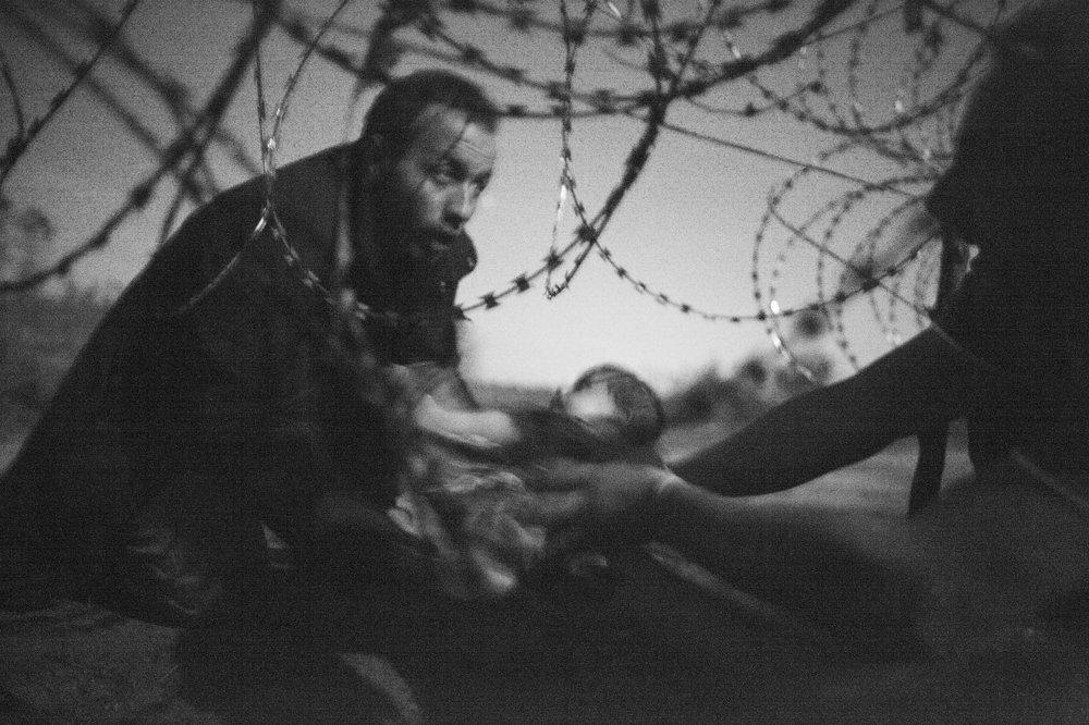 Utečenec podáva dieťa cez ostatnú zábranu na hraniciach v Röszke. Vítazná fotografia - Warren Richardson/World Press Photo