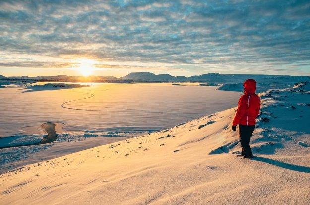 Východ slnka na zamrznutom jazere Mývatn na Islande.