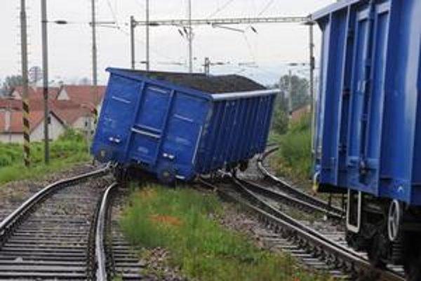 V stredu vykoľajený vagón s uhlím.