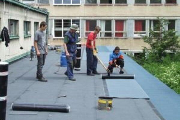 Na streche obchodnej akadémie učni s majstrom odborného výcviku Jozefom Klimom vymieňajú poškodenú lepenku.