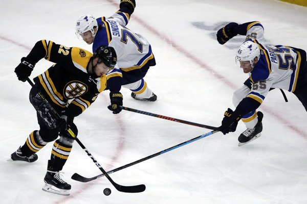 Ľavé krídlo Bostonu Bruins Peter Cehlárik (22) a hráči St. Louis Blues Oskar Sundqvist (70) a Colton Parayko (55) počas zápasu zámorskej NHL 17. januára 2019 v Bostone.