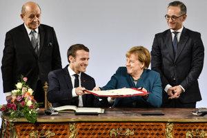 Nemecká kancelárka Angela Merkelová a francúzsky prezident Emmanuel Macron podpísali novú zmluvu o priateľstve medzi oboma krajinami. Nad nimi sú ministri zahraničných vecí Jean-Yves Le Drian (Vľavo) a Heiko Maas.