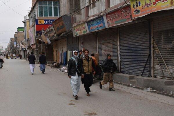 Ľudia prechádzajú popri obchodoch zatvorených na protest po zabití aktivistu Armana Loniho v Pakistane.