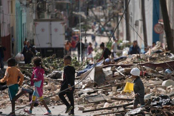 Deti prechádzajú popri troskách po tornáde, ktoré zasiahlo Havanu.