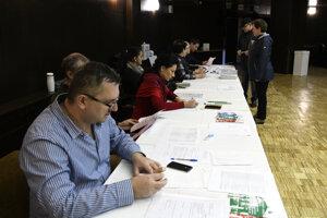 Členovia volebnej komisie v Ilave kontrolujú totožnosť voličov.