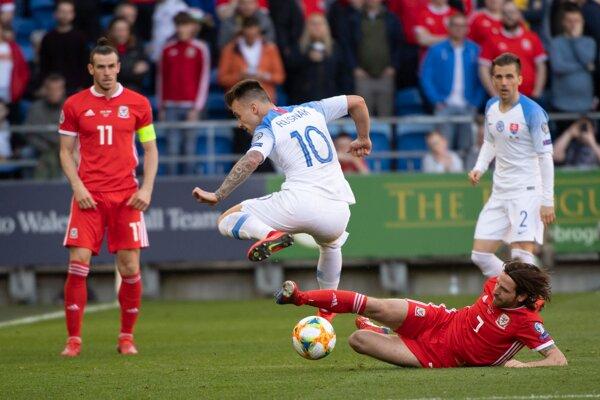 Albert Rusnák v súboji s hráčmi Walesu, prizerá sa jeho spoluhráč Peter Pekarík.