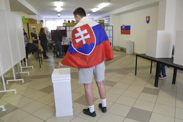 Volič z Brna so slovenskou vlajkou vhadzuje obálku s hlasovacím lístkom do volebnej schránky v 2. kole prezidentských volieb vo volebnej miestnosti v obci Kúty.