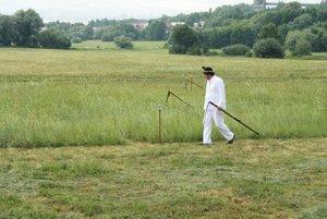 Súťažiaci kontroluje trávu po búrke .