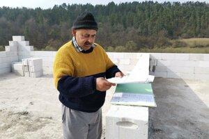 Vojtech ukazuje povolenia i projekt domu.