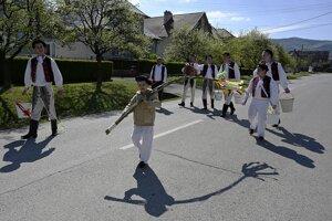 Mládenci v ľudových krojoch z obce Selec neďaleko Trenčína oblievajú dievča na Veľkonočný pondelok.