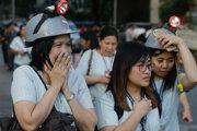 Zamestnankyne s helmami evakuujú z administratívnej budovy v Manile.