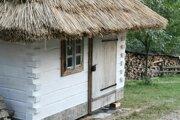 Prenosná replika dreveničky so slamenou strechou.