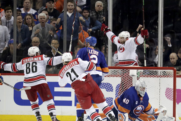 Jordan Staal (za bránou) sa raduje z rozhodujúceho gólu v predĺžení zápasu s New York Islanders.