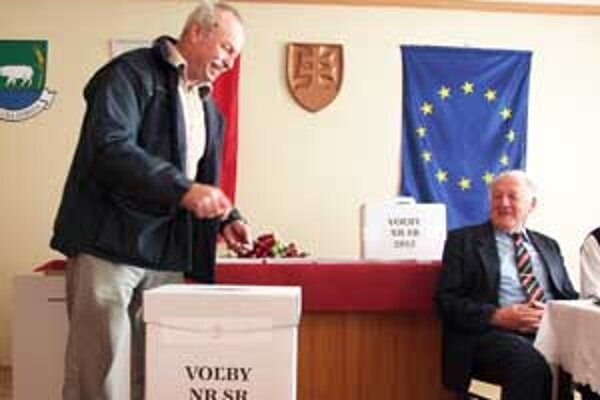 Volič vhadzuje hlasovací lístok do volebnej urny v Revúckej Lehote.