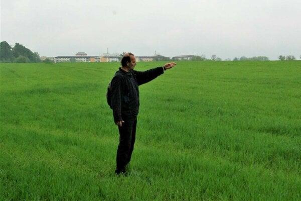 Róbert Tomčík ukazuje smerom, kde by mala začať výstavba domov.