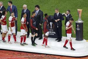 Hráči Arsenalu si preberajú pamätné medaily.