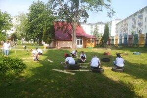Dobrovoľníci v materskej škole na Budovateľskej ulici v Prešove sadia popínavé rastliny a stavajú hmyzí hotel.