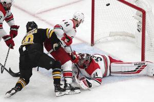 Na snímke vľavo švédsky útočník Bostonu Marcus Johansson strieľa gól, dole český brankár Petr Mrázek v prvom zápase finále 3. kola play off Východnej konferencie hokejovej NHL Boston Bruins - Carolina Hurricanes (5:2) v noci na 10. mája 2019.