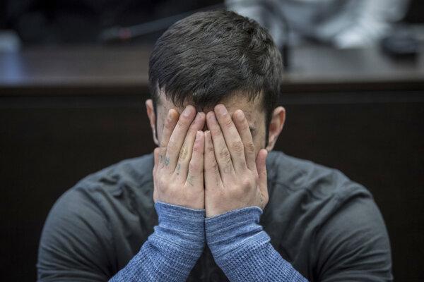 Ali Bashar, migrant z Iraku a odsúdený vrah 14-ročnej nemeckej školáčky, si zakrýva tvár pred súdom vo Wiesbadene.
