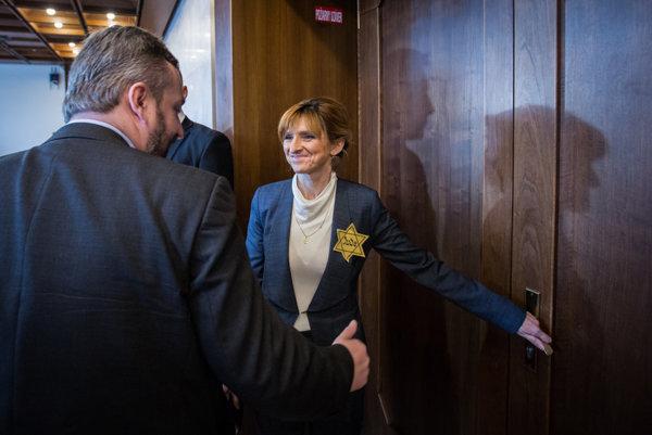 Viera Dubačová a Ondrej Dostál vchádzajú do rokovacej miestnosti s odznakom žltej hviezdy.
