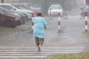 Žena prechádza cez ulicu počas búrky.