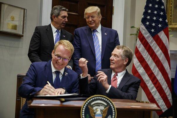 Americký prezident Donald Trump a veľvyslanec EÚ v USA Stavros Lambrinidis stoja za fínskym predstaviteľom Janim Raappanom ,ktorá vedľa amerického obchodného splnomocnenca Roberta Lighthizera podpisuje dohodu.